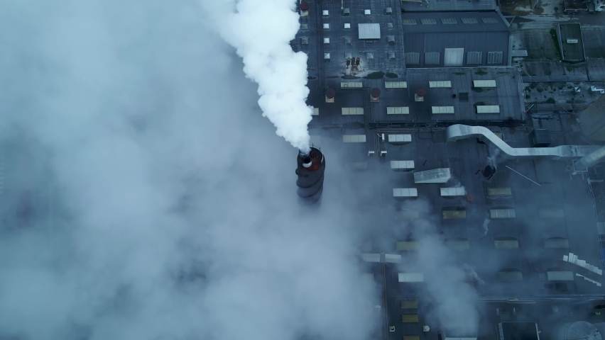 Large factory with white steam and smoke coming from chimneys and smokestacks. 4K aerial footage.   Shutterstock HD Video #1065601054