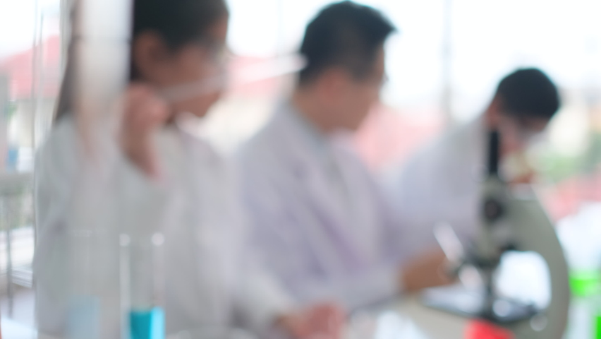 Young scientist girl concentrate to test color chemical in classroom with her classmate working in the background. | Shutterstock HD Video #1065614548