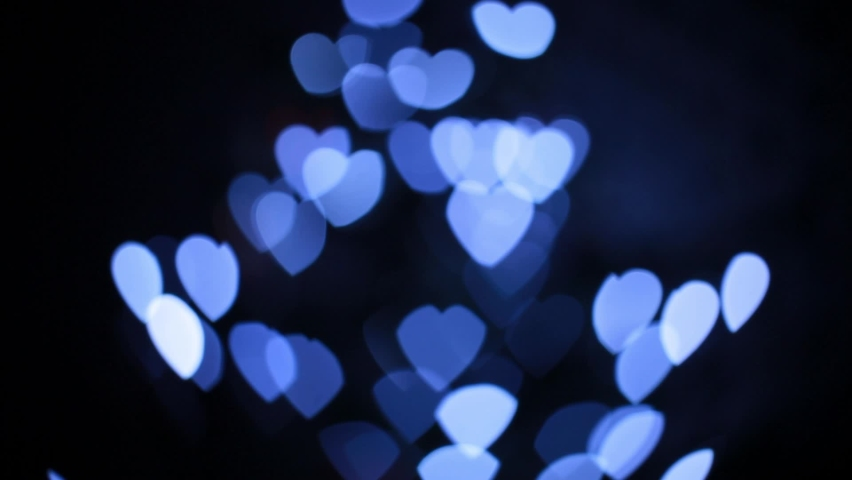 Blue heart. Valentine's Day. Beautiful holiday lights in the shape of a heart. Blurred background. Flashing abstract colored circles defocused the Christmas light video. Blurred fairy lights | Shutterstock HD Video #1065614575