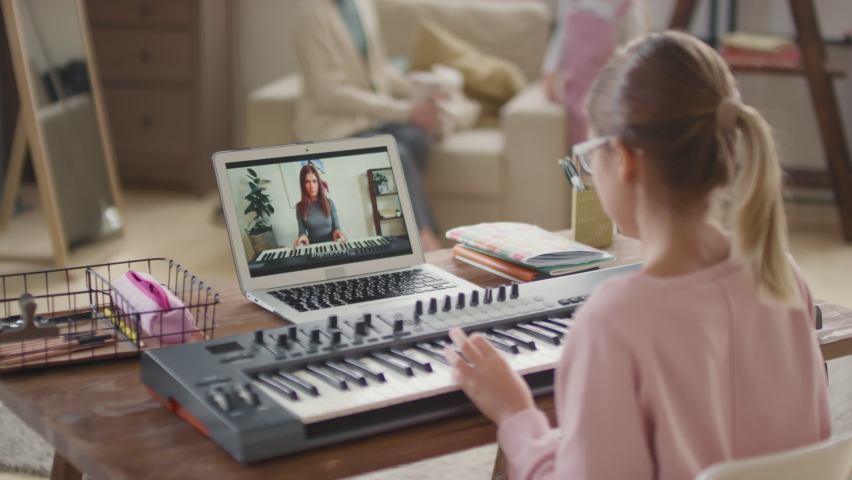 Over-the shoulder footage of 12-year-old girl having online music lesson via laptop learning to play keyboard repeating after teacher while woman and little girl playing on sofa in blurred background | Shutterstock HD Video #1065614743