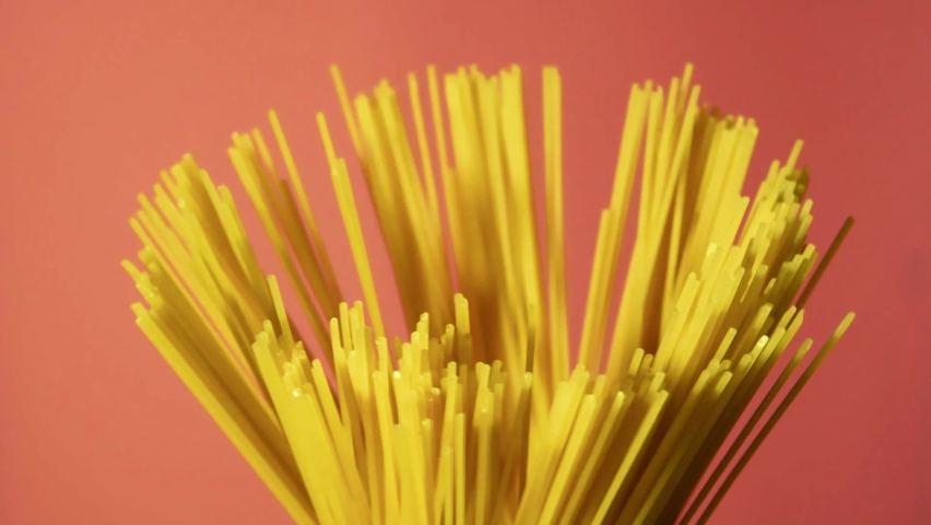 Spaghetti noodles isolated on pink background. Slow motion. Raw pasta. Rotating left. | Shutterstock HD Video #1065614752