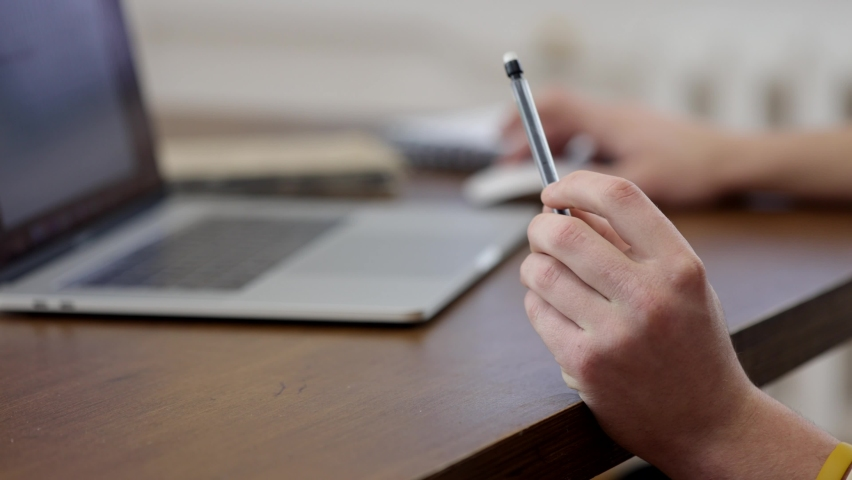 Close up of male hands working at a laptop. In one hand, the guy turns a pen. The concept of working with information. | Shutterstock HD Video #1065615250