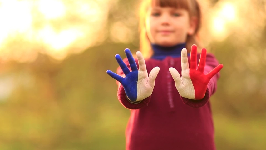 Joyful girl waving hands painted in France flag colors and say hello outdoor at sunset background   Shutterstock HD Video #1065620044