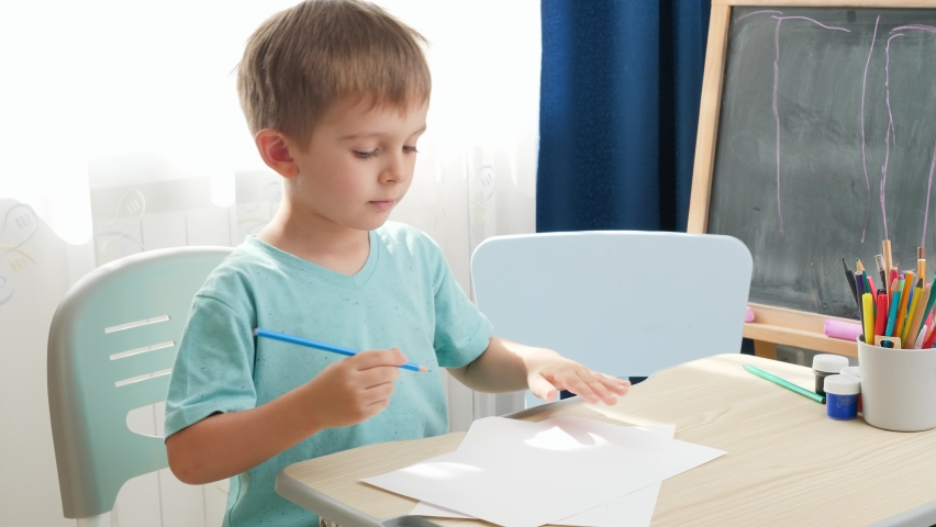 Concentrated little boy drawing or writing with pencil while sitting behind school desk at home or school classroom. Concept of education and remote school at home during lockdown and self isolation | Shutterstock HD Video #1065620437
