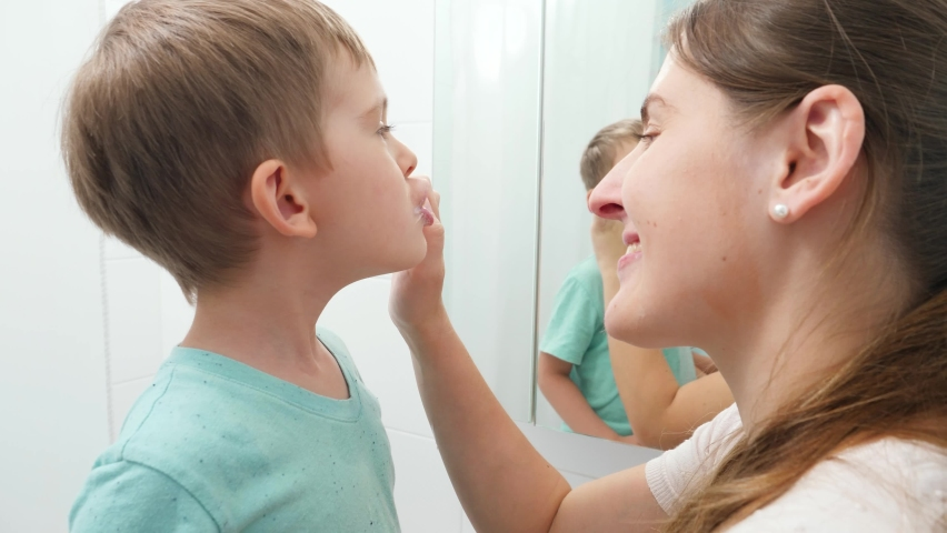 Young caring mother brushing and cleaning teeth of her little son. Parents and children taking care of teeth health and hygiene. | Shutterstock HD Video #1065620668