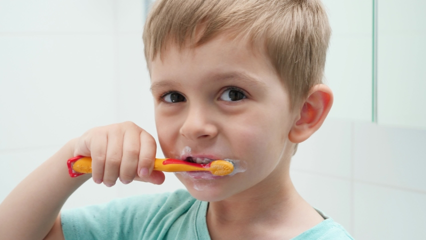 Portrait of funny toddler boy cleaning and brushing teeth at morning. Concept of teeth hygiene and child healthcare. | Shutterstock HD Video #1065620671