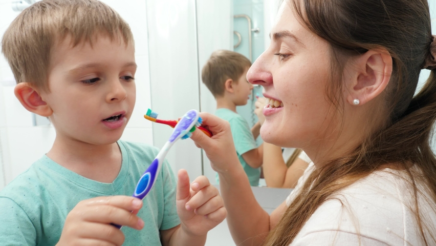 Smiling little boy with young mother brushing teeth and cleaning mouth with toothbrushes to each other. Family having fun while taking care of teeth hygiene and healthcare. | Shutterstock HD Video #1065620674