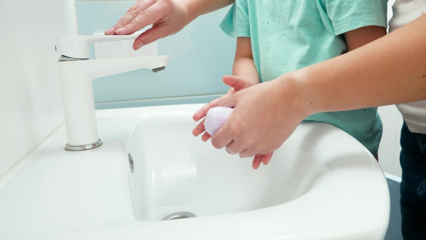Little toddler boy wsahing hands with young mother. Closeup of child cleaning and washing hands with antibacterial soap and water. | Shutterstock HD Video #1065620683