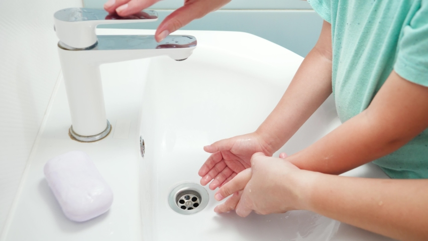 CLoseup of mother teaching and showing her little son how to wash hands. Child using antibacterial soap while washing hands in bathroom. | Shutterstock HD Video #1065620686