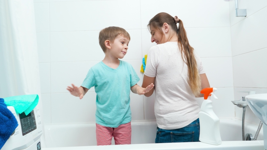 Funny toddler boy dancing and having fun while mother doing housework and washing walls in bathroom. | Shutterstock HD Video #1065620695