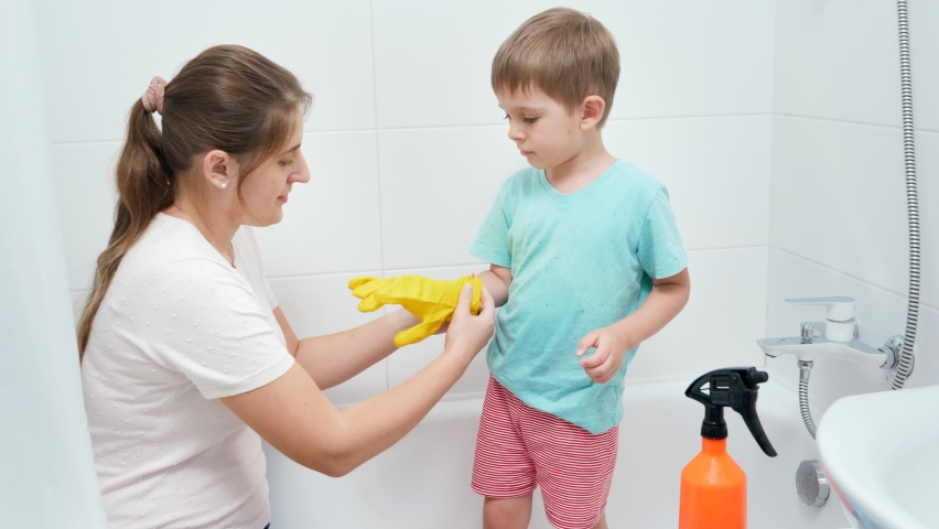 Little toddler boy wearing and putting on protective rubber gloves before cleaning and washing bath in bathroom | Shutterstock HD Video #1065620698