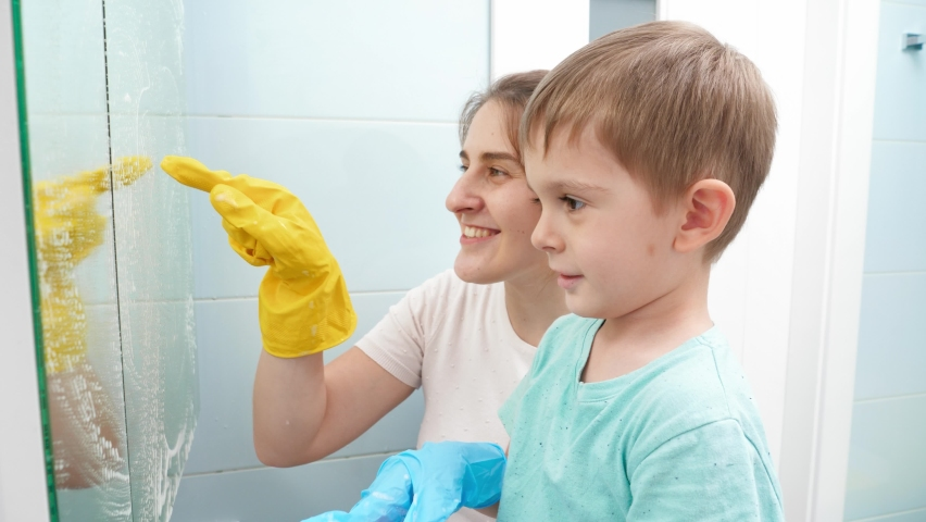 Happy mother with little son drawing on dirty mirror while doing housecleanup and housework. Family having good time together | Shutterstock HD Video #1065620704