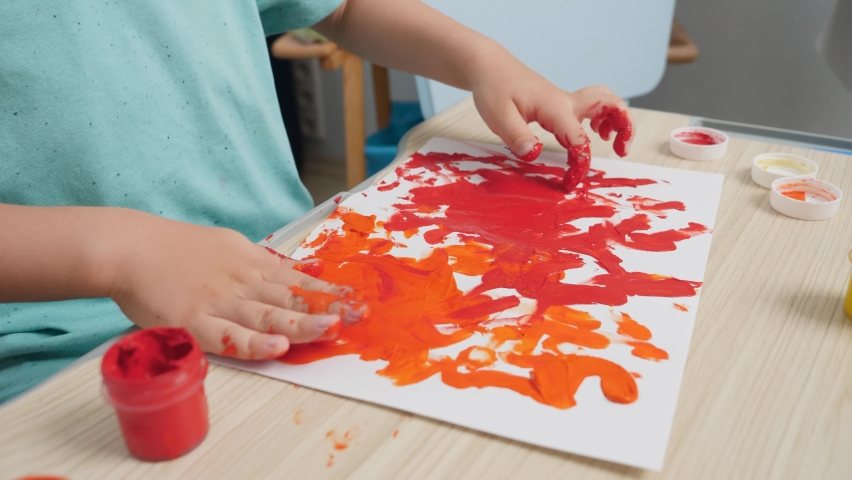 Closeup of little boy sitting behind school desk and drawing with fingers covered in colorufl paint. Concept of child education,, creativity development and art at home. | Shutterstock HD Video #1065620707