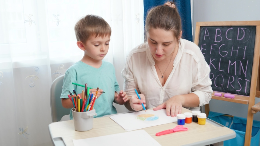 Little toddler boy with young mother drawing and painting with colorful pencils. Doing homework and edcucation with parents | Shutterstock HD Video #1065620713