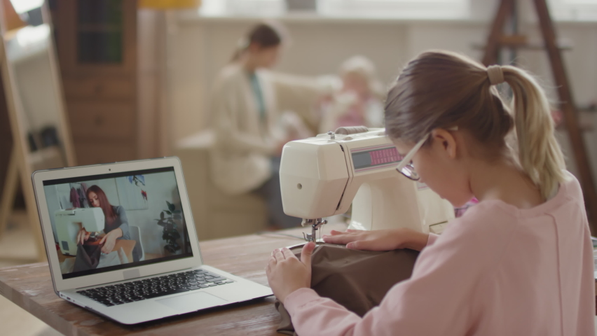 Medium close-up of young girl having online sewing lesson via laptop using cloth and sewing machine, while her mom and little sister playing on sofa in background | Shutterstock HD Video #1065622888
