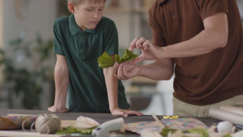 Tilting-up slowmo medium shot of caucasian man explaining his little son how to make paper bows for flying kite tail standing together in cozy living room | Shutterstock HD Video #1065623818