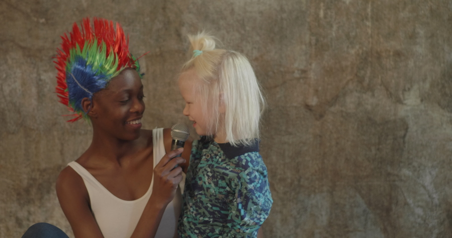 African American woman in white bodysuit and jeans in bright multicolored punk wig and white blond boy singing karaoke with microphone and fooling around. Young mother and foster child love each other | Shutterstock HD Video #1065624637