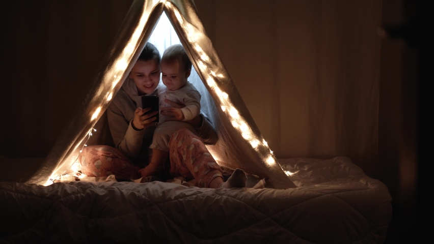 Authentic cute mom with chubby babe infant girl in tent at home. young woman use smartphone with kid 6-12 months old sit in wigwam at night. Family, Childhood, Motherhood, Comfort and Safety concept. | Shutterstock HD Video #1065624907