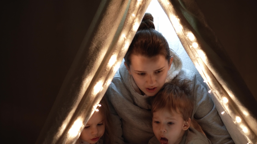 Authentic tender cute mom and preschool kids boy and girl in tent at home. young woman read book to children 2-4 years old in wigwam at night. Family, Childhood, Motherhood, Comfort and Safety concept | Shutterstock HD Video #1065624910