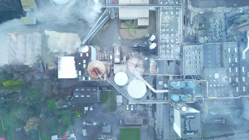 Top down view over a large factory with smoke and steam coming from its chimneys.   Shutterstock HD Video #1065625297