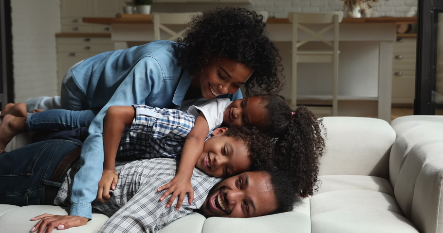 African young parents with preschool 5s siblings adorable son daughter lying on couch together laughing tickling each other looking at camera having fun feel overjoyed. Happy family portrait concept Royalty-Free Stock Footage #1065627496