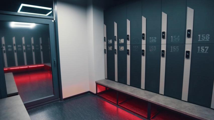 Walking inside dressing rooms of professional modern gym club. Locker cabins. Changing room. Fitness center design.