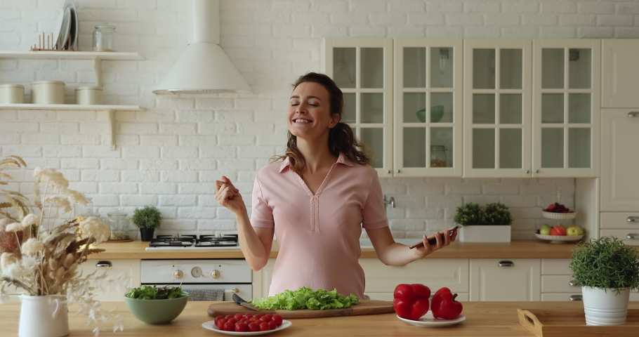 Happy housewife carefree young woman holding smartphone listen favourite music dancing moving feel untroubled while cooking in modern domestic kitchen alone. Hobby, food preparation, lifestyle concept