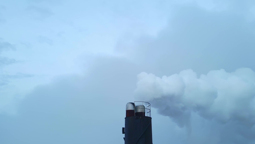 White smoke streaming out of a large industrial smoke stack at a factory. Close up aerial footage.   Shutterstock HD Video #1065656164