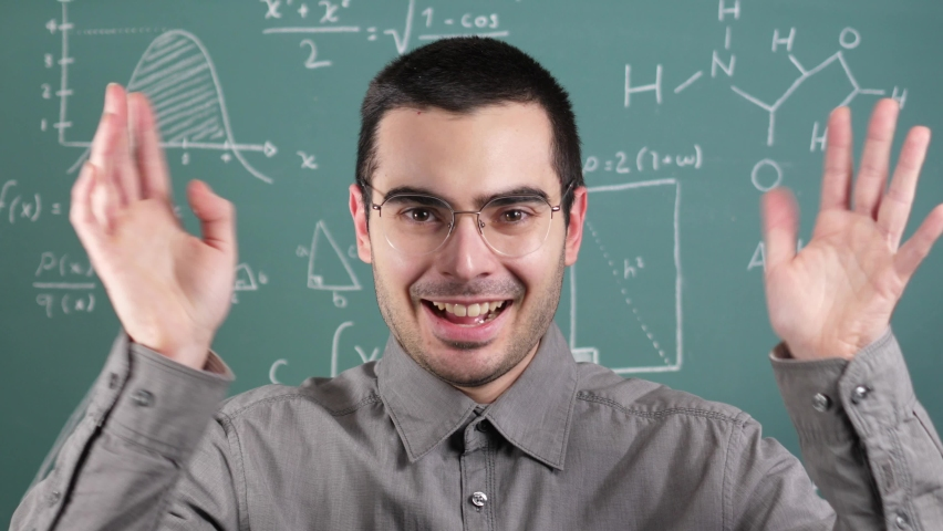 Teacher teaching in front of a blackboard looking at the camera | Shutterstock HD Video #1065676315