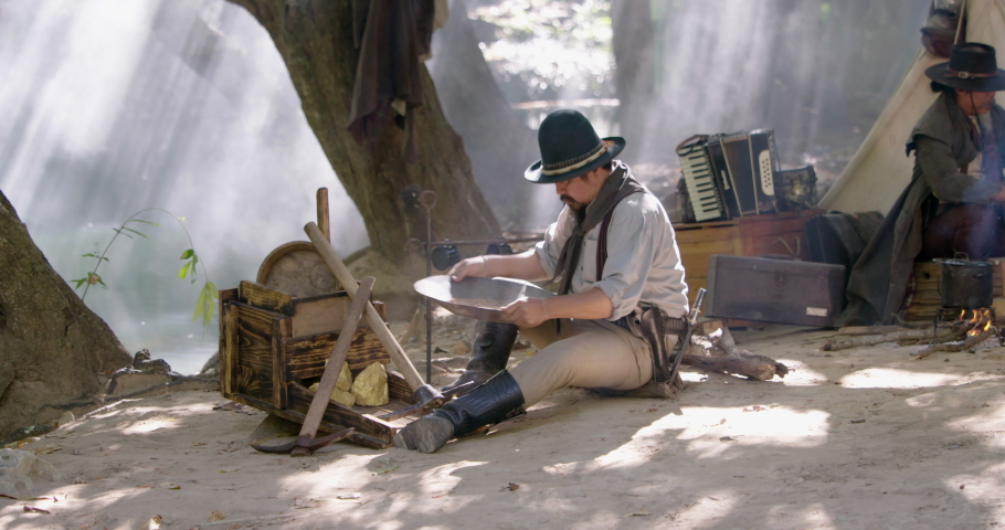 Gold digger wearing on cowboy hat and cowboy boots sitting using gold panning to refining the gold metal particles  while boiling the coffee flask above fire | Shutterstock HD Video #1065679120