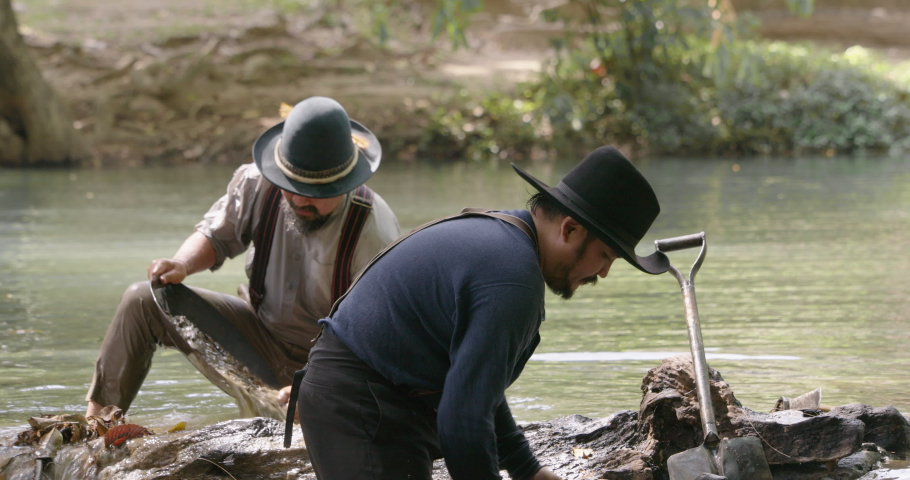 Gold digger wearing on cowboy hat standing in the water one using shovel digging soil from water pouring to gold panning to refining the gold metal particles   | Shutterstock HD Video #1065679144