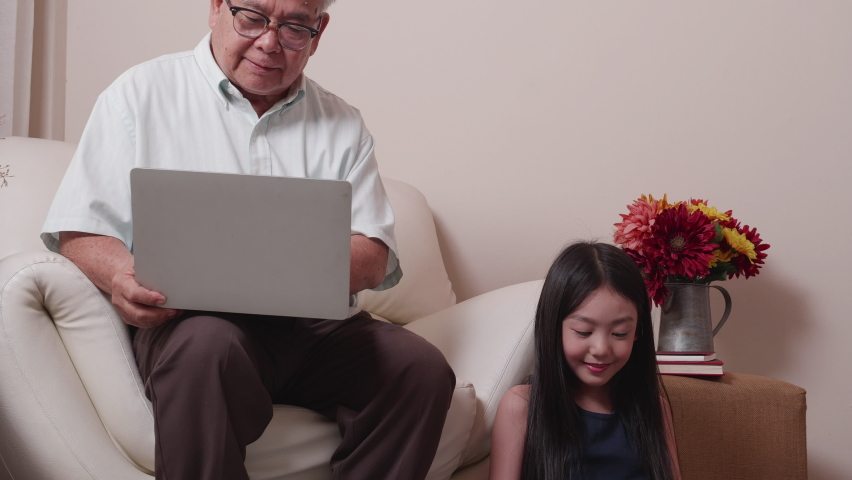 Happy Asian retirement grandfather and pretty granddaughter watching e-book for learning to education together by laptop. Happy Family educational at home concept. Technology and education. | Shutterstock HD Video #1065679282