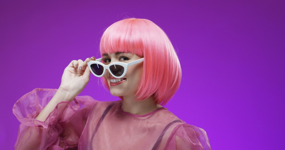 Portrait of pretty extraordinary young Caucasian woman in pink wig taking off fancy sunglasses and blinking to camera. Close up of happy cute female model smiling on bright background. Barbie concept.