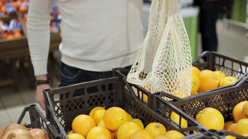 Close up of man hands puts oranges into eco string bag at product store | Shutterstock HD Video #1065685699