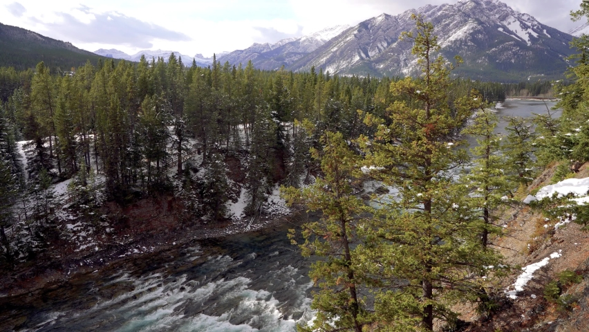 Bow River and Bow Falls in snowy autumn sunny day. View from Surprise Corner Viewpoint, Mount Norquay in the background. Banff National Park, Canadian Rockies. | Shutterstock HD Video #1065686293