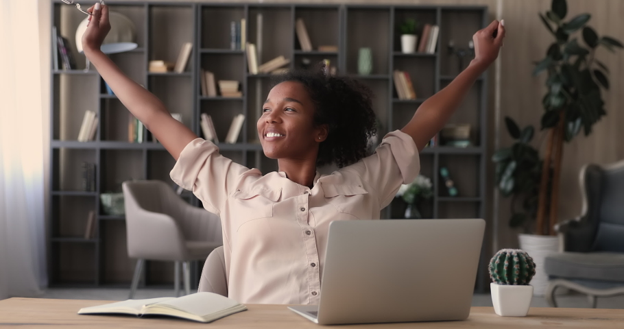 Smiling african businesswoman or student finished computer work, take off glasses stretching relaxing seated at workplace feeling stress relief, satisfied by project accomplishment, task done in time Royalty-Free Stock Footage #1065694552