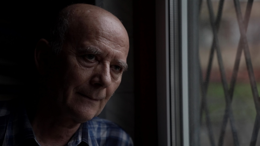 Grandfather is watching at window at daytime, resting in his apartment | Shutterstock HD Video #1065703876