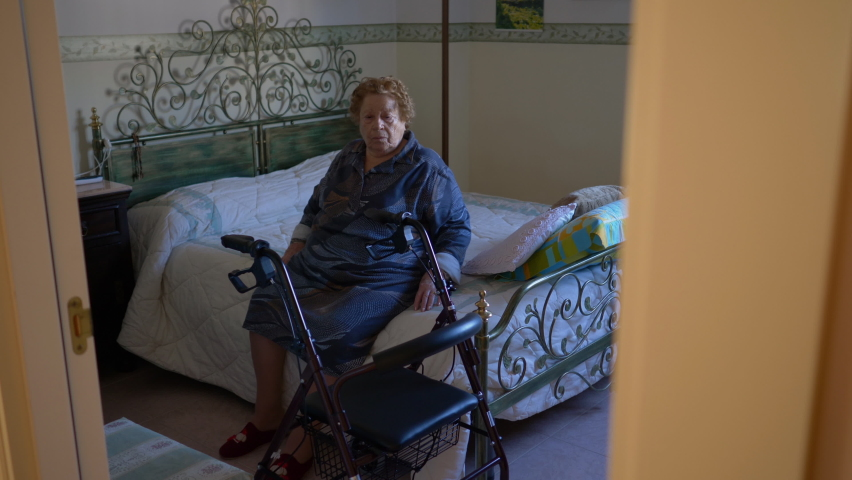 Elderly woman gets out of bed using the walker. It is a very useful tool in the presence of motor problems. | Shutterstock HD Video #1065704725
