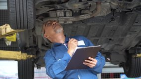 asian mechanic senior man holding clip board checking list to brake ,tyre, undercarriage of car in workshop at auto car repair service center with lift. car engineer old man inspection vehicle details