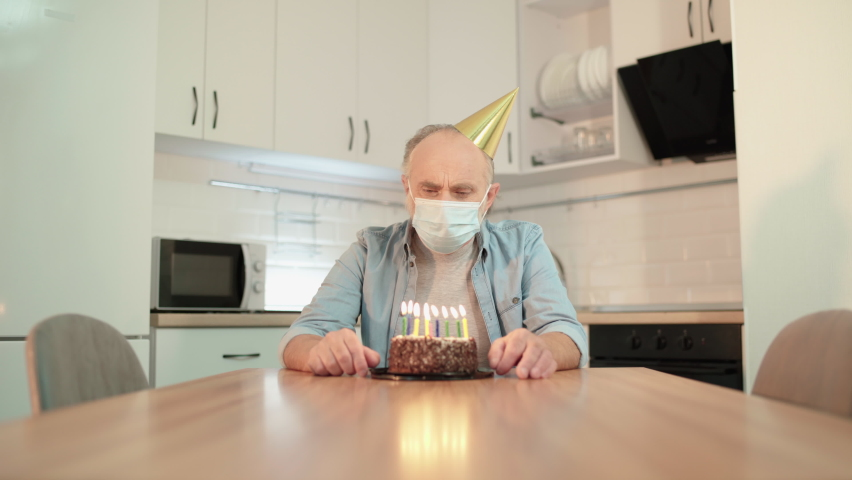 Unhappy grandpa in mask looking at birthday cake, social distancing, isolation | Shutterstock HD Video #1065706183