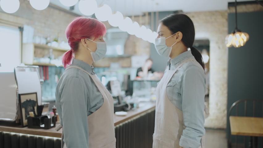 Coffee shop employees bumping elbows, greeting during coronavirus pandemic