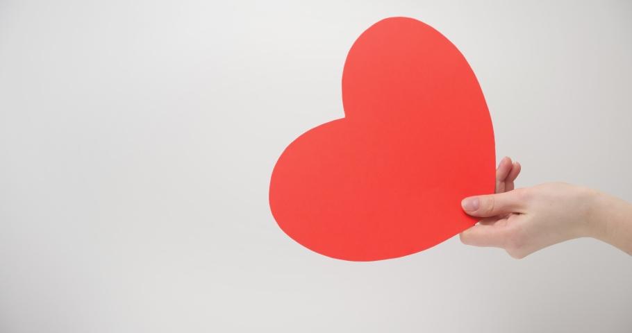 Red cardboard heart in a woman's hand, like it | Shutterstock HD Video #1065706738