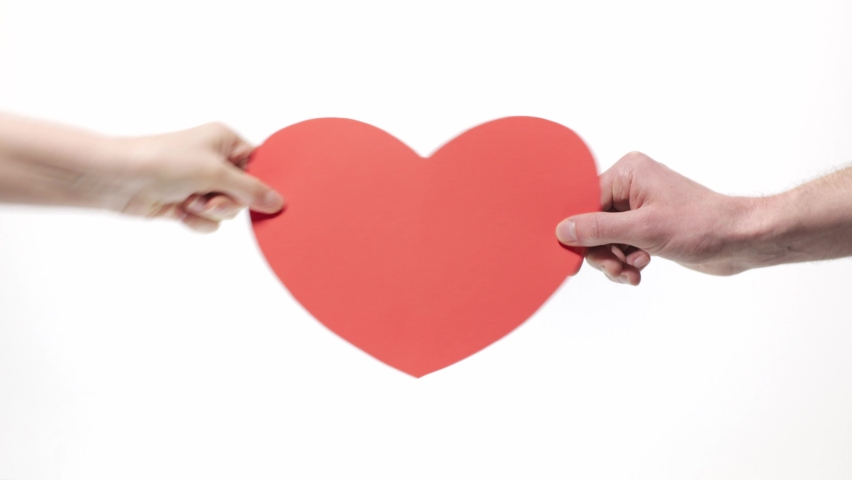 Red cardboard heart in a woman's hand, gives a man's hand | Shutterstock HD Video #1065706747