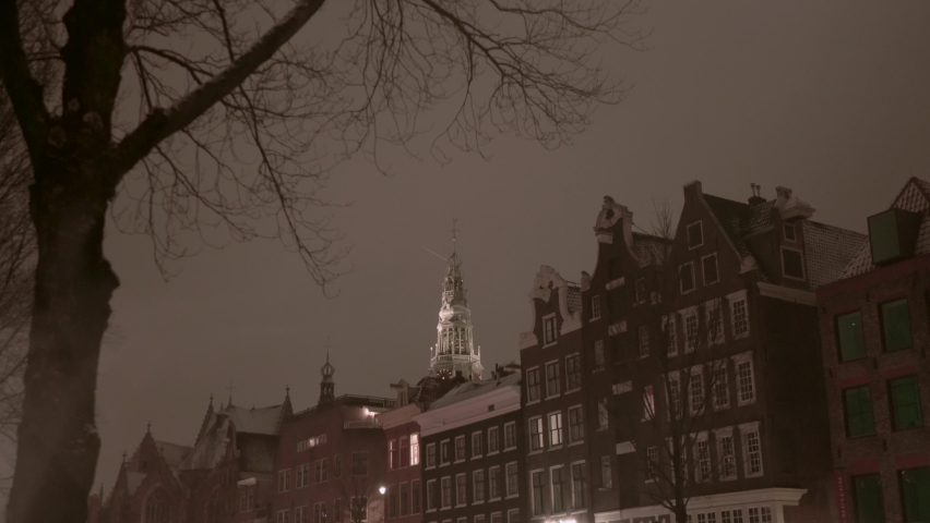 AMSTERDAM, NETHERLANDS - JANUARY 17, 2021: View on Old Church in de Wallen Red Light district in the historic city centre of Dutch capital Amsterdam during Covid-19 Corona lockdown. Cold, snow, winter   Shutterstock HD Video #1065710344