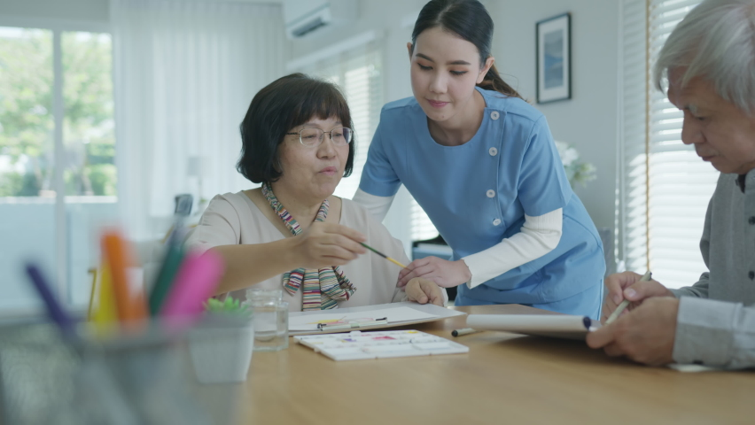 Attractive young senior asian citizen couple sit at home watercolor painting artwork on desk table with nurse feeling happy in mental health therapy or asia older people quarantine activity lifestyle. | Shutterstock HD Video #1065713920