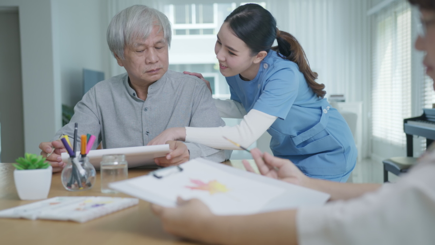 Attractive young senior asian citizen couple sit at home watercolor painting artwork on desk table with nurse feeling happy in mental health therapy or asia older people quarantine activity lifestyle. | Shutterstock HD Video #1065713926