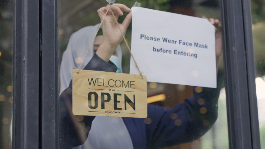 Young Asian Muslim woman in hijab wearing protective face mask, attach the sign on the shop front door to remind customer wear the face mask before entering for prevent the spread of coronavirus | Shutterstock HD Video #1065717268