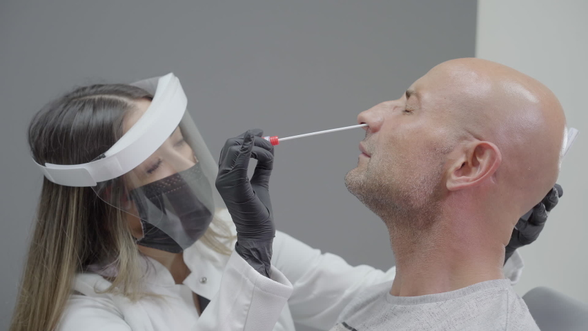 Virus Swab Test. Female doctor doing a nasopharyngeal swab test to a male patient. The doctor wearing medical protective equipment: mask, protective glasses, gloves and smock. Royalty-Free Stock Footage #1065717394