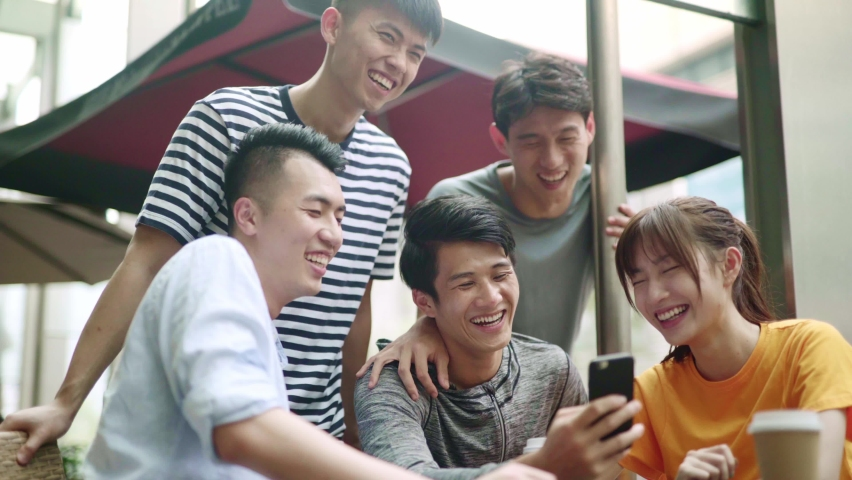 group of young asian adults looking at cellphone together happy and smiling Royalty-Free Stock Footage #1065732268