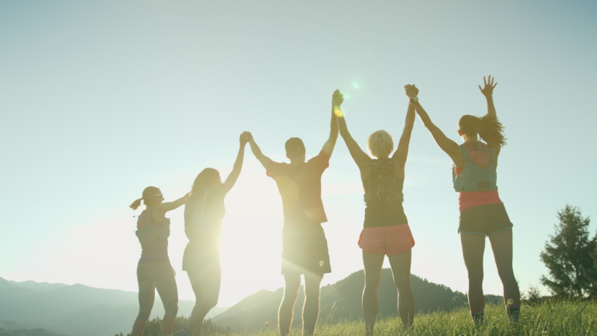 A team of runners jumps in the air together on the top of the hill with mountain view in a beautiful golden sunset light. Runners holding their hands and together reach the goal. Royalty-Free Stock Footage #1065743107